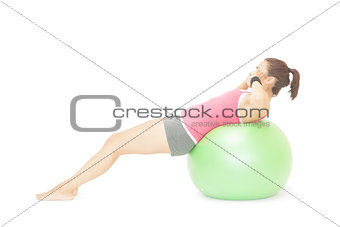 Attractive sporty brunette doing sit ups on exercise ball