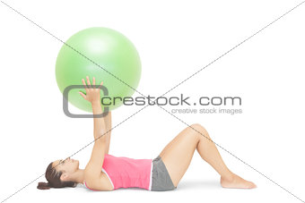 Attractive sporty brunette lying on floor holding exercise ball