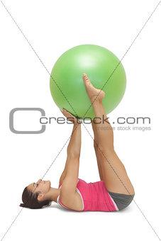 Calm sporty brunette lying on floor holding exercise ball between legs