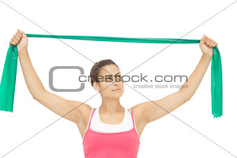 Calm sporty brunette stretching with resistance band