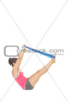 Attractive sporty brunette exercising with resistance band