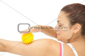 Calm sporty brunette touching arm with yellow massage ball