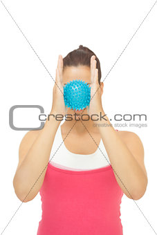Sporty brunette holding blue massage ball between hands