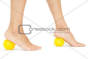 Close up of female feet touching yellow massage balls