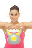 Happy sporty brunette holding grey and yellow kettlebell
