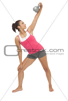 Attractive sporty brunette holding grey kettlebell