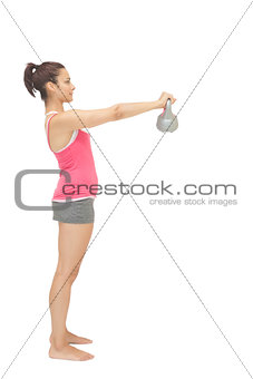 Attractive toned brunette holding grey kettlebell