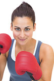 Content sporty brunette wearing red boxing gloves
