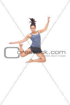 Attractive sporty brunette jumping in the air
