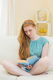 Pretty redhead reading a book on the sofa