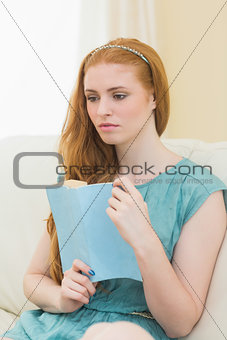 Thoughtful redhead holding a book on the sofa