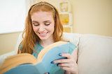 Happy redhead reading a book on the couch