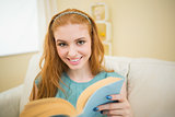 Happy redhead reading a book on the couch looking at camera