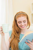 Cheerful redhead reading a book on the couch and holding mug
