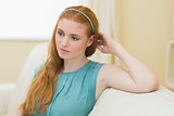 Thoughtful redhead sitting on the couch