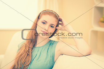 Thoughtful redhead sitting on the couch smiling at camera