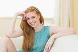 Happy redhead sitting on the couch smiling at camera