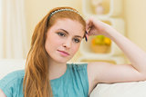 Thinking redhead sitting on the couch