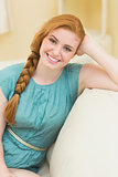 Smiling redhead sitting on the couch looking at camera