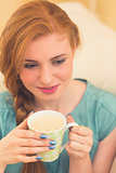 Smiling redhead sitting on the couch having coffee