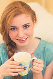 Smiling redhead sitting on the couch having coffee looking at camera