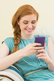 Happy redhead sitting on the couch using smartphone