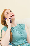 Laughing redhead sitting on the couch making a call