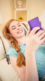 Smiling redhead lying on the couch sending a text