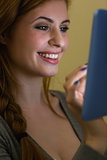 Smiling redhead sitting on the sofa holding tablet pc at night