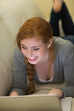 Smiling redhead lying on the couch using her laptop at night
