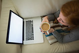 Redhead lying on the couch looking at laptop having coffee