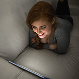 Smiling redhead lying on the couch using her tablet pc