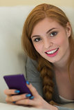Happy redhead lying on the sofa sending a text