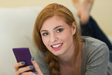 Pretty redhead lying on the sofa sending a text smiling at camera