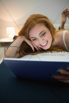 Attractive redhead using digital tablet lying on her bed