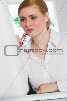 Focused businesswoman working at her desk holding glasses
