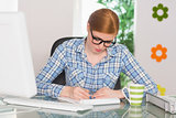 Redhead writing on notepad at her desk