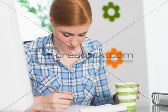 Focused redhead writing on notepad at her desk and holding coffee