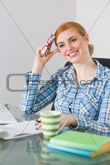 Thoughtful redhead sitting at her desk looking away holding reading glasses
