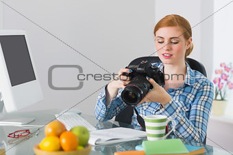 Thoughtful photographer sitting at her desk looking at camera