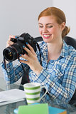 Happy photographer sitting at her desk looking at camera