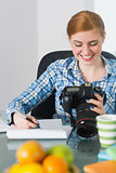 Smiling photographer sitting at her desk looking at camera