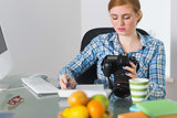 Serious photographer sitting at her desk looking at camera