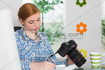 Focused photographer sitting at her desk holding her camera