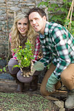 Happy couple crouching in their garden
