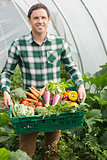 Young man presenting proudly some vegetables