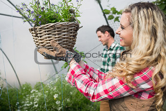 Beautiful woman touching a hanging flower basket