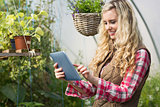 Pretty woman using her tablet in a green house