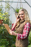 Phoning woman holding a clipboard in her green house