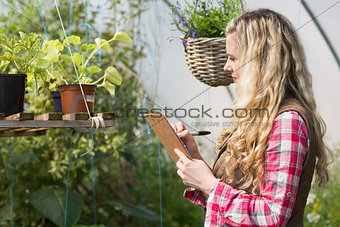 Blonde woman using a clipboard and taking notes